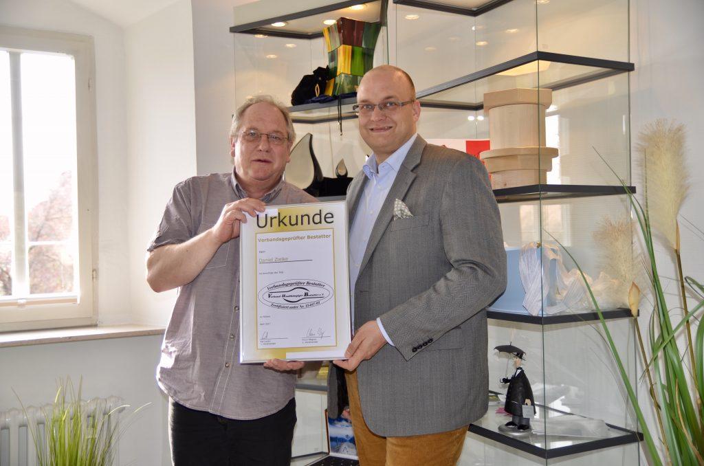 H.-J. Möller (Geschäftsführer des Bestatterverbandes VuB e.V.) überreicht dem Bestatter Daniel Zielke (rechts) die Urkunde zur Zertifizierung.
